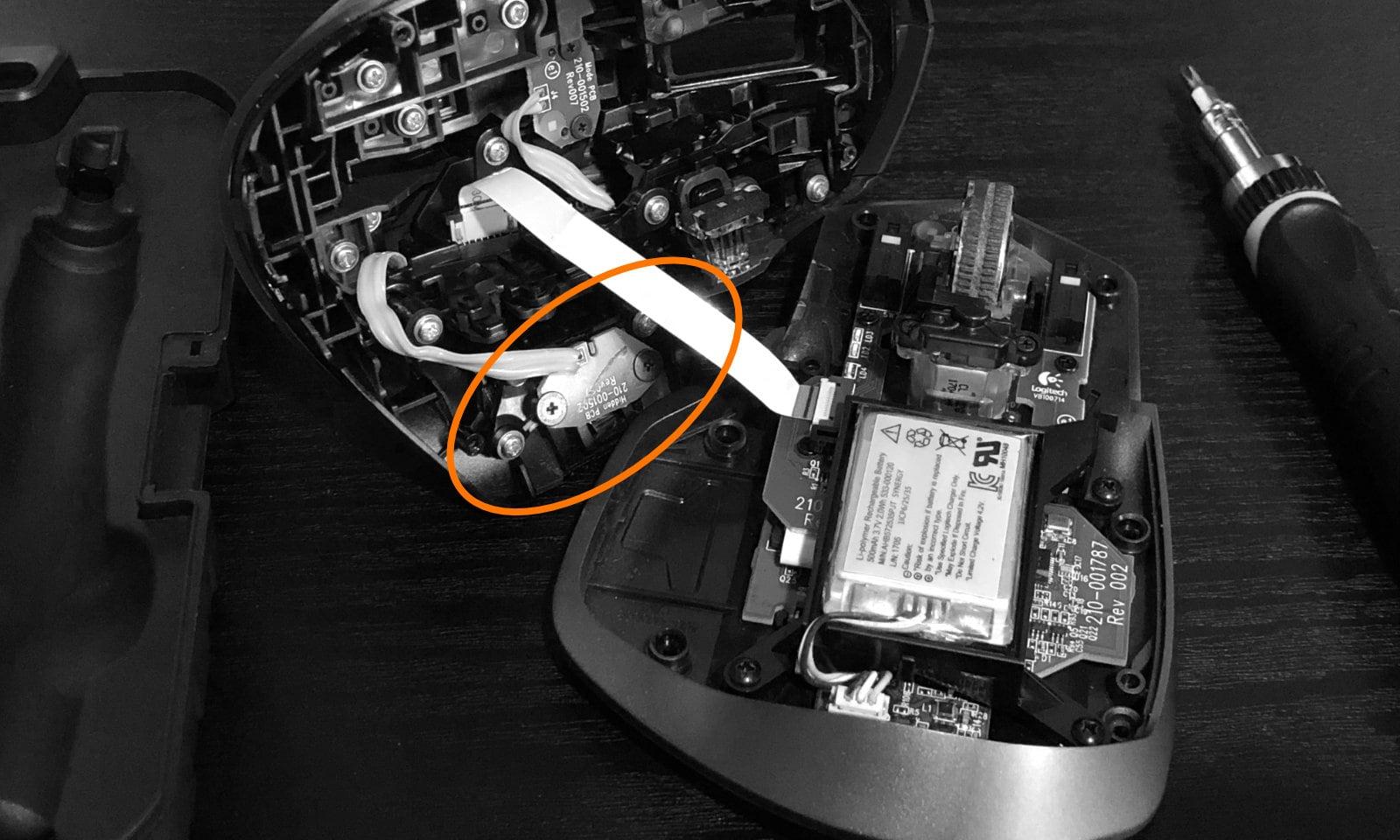 解体して上下のパーツに分かれた状態のマウスの写真。ケーブルで繋がっている。親指ボタンのパーツが丸で囲われている